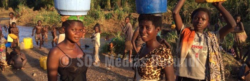 Des femmes et enfants vont puiser de l'eau dans la rivière Lusenda.