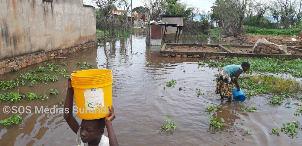 Une jeune femme puisse les eaux des inondations dans un quartier de Rumonge