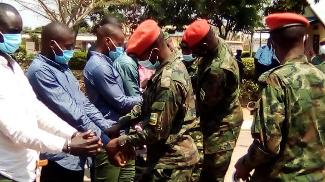 Des militaires rwandais enlèvent les menottes aux 19 anciens rebelles avant de les rendre à l'armée burundaise